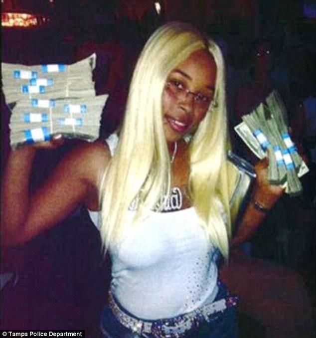 Rashia Wilson poses with Stacks of money
